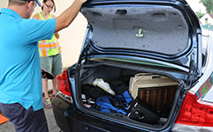 Removing waste items from trunk of car