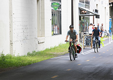 Two bicyclists ride on a paved trail in front of an industrial building. A Midtown Greenway sign hangs above them.