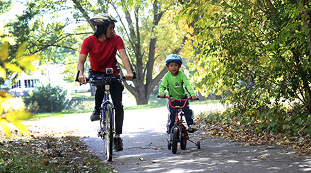 A man and child riding bikes on a trail path