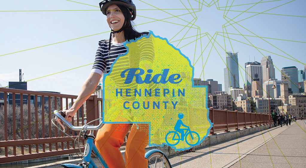 Ride Hennepin County. Photo of a woman riding her bike along a bridge near downtown Minneapolis.