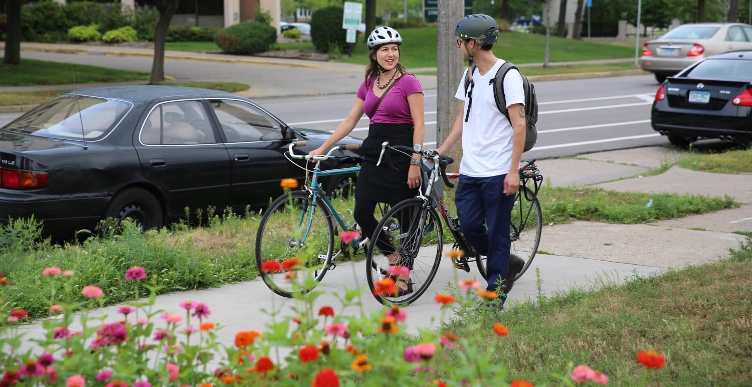 Two people walking their bikes down a sidewalk with flowers in the foreground