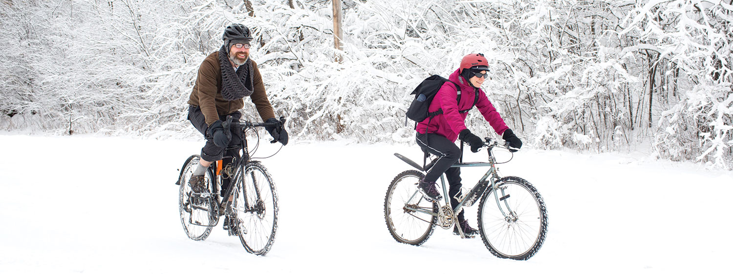 two bikers riding through the snow