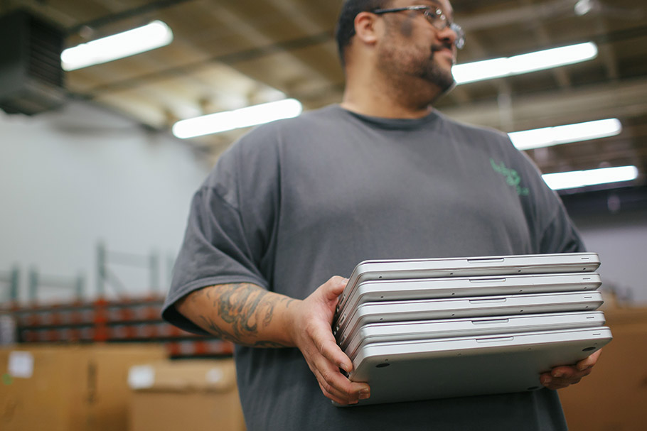 Man holding stack of closed laptops