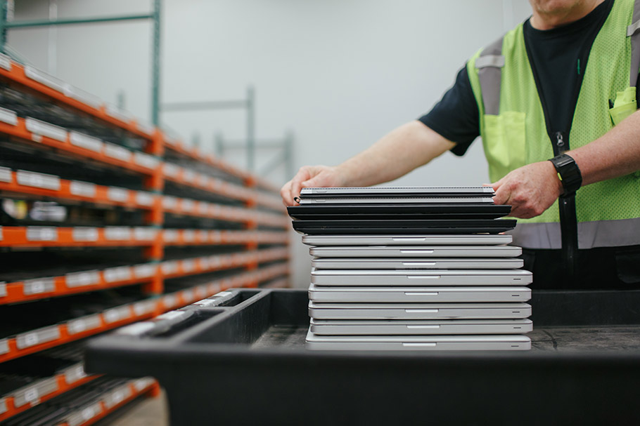 Worker in safety vest with cart of laptops