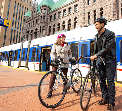 Two people with bikes standing in front of the lighte rail in downtown Minneapolis