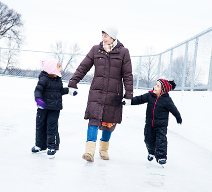 Mom holding the hands of two kids bundled up on ice skating rink