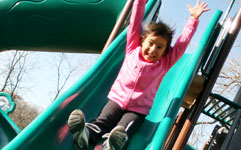 Young girl sliding down slide