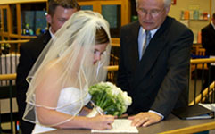 couple signing wedding license with officiant