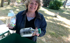 woman putting recycling into recycling container